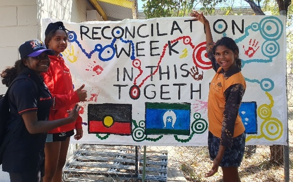 Indigenous girls holding Reconciliation Week sign